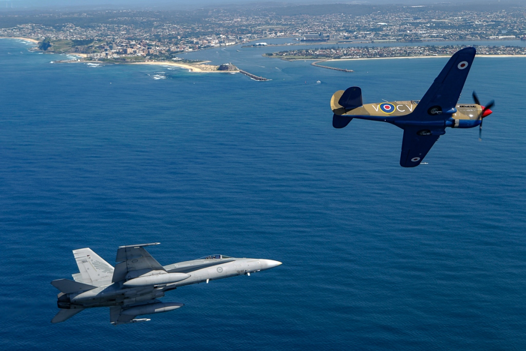 RAAF F/A-18A Hornet 3SQN A21-21 with P-40E CV-V with Newcastle in the back ground.@CoA Credit RAAF Official