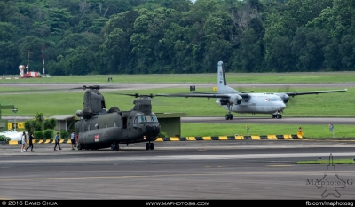 Joyride participants boarding a CH-47D Chinook while a Fokker 50 taxies for take off
